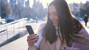 Portret uśmiechnięta brunetki kobieta w eleganckim żakiecie i szaliku, na miasto ulicie z unsing smartphone zbiory