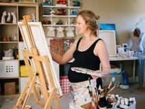 Portret uśmiechać się białego Kaukaskiego młodego kobieta w ciąży obrazu rysunkową pozycję przy sztalugą w domowym studiu zdjęcie stock