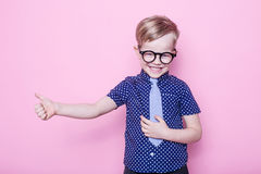 Portret uśmiechać się chłopiec w śmiesznym krawacie i szkłach troszkę szkoła preschool Moda Pracowniany portret nad różowym tłem Zdjęcie Royalty Free