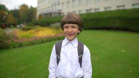Portret uśmiechać się szczęśliwego ślicznego chłopiec ucznia śmia się kamera outdoors z plecakiem, stopnia uczeń ma zabawę zdjęcie wideo