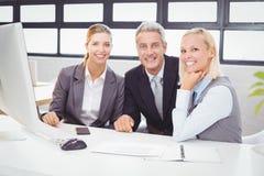 Portret uśmiechnięci biznesowi profesjonaliści pracuje przy komputerowym biurkiem obrazy royalty free