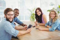 Portret uśmiechnięci biznesowi profesjonaliści używa technologię przy biurkiem obraz stock