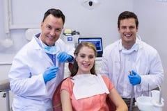 Portret uśmiechnięci dentyści i żeński pacjent Zdjęcia Stock