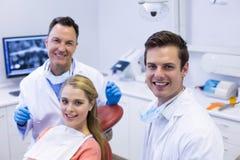 Portret uśmiechnięci dentyści i żeński pacjent Fotografia Stock