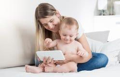 Portret uśmiechnięci potomstwa matkuje dopatrywanie film na pastylka komputerze z jej dziecko synem zdjęcie stock