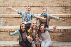 Portret uśmiechnięci szkolni ucznie siedzi na schody ma zabawę w kampusie Zdjęcie Stock