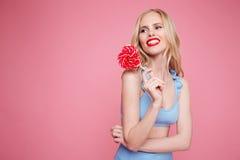 Portret uśmiechnięta ładna blondynki kobieta w swimsuit pozuje z sercem kształtował lizaka i patrzeć daleko od fotografia stock