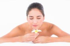 Portret uśmiechnięta ładna brunetka na masażu stole z kwiatami Zdjęcie Stock