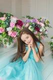 Portret uśmiechnięta ładna mała dziewczynka w turkusowej sukni w studiu dekorował kwiaty Zdjęcia Stock