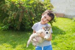 Portret uśmiechnięta śliczna chłopiec z agry łuskowatym szczeniakiem Obrazy Royalty Free