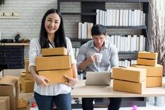 Portret uśmiechnięta azjatykcia młoda kobieta stoi w domowym biurze z kartonami obraz stock