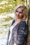 Portret uśmiechnięta blond młoda kobieta opiera przeciw drzewu Fotografia Stock