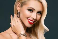 portret uśmiechnięta blondynki kobieta pozuje w bransoletce i kolczykach, fotografia royalty free