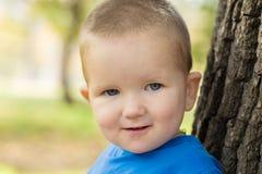 Portret uśmiechnięta chłopiec ubierał w błękitnym pulowerze na słonecznym dniu fotografia stock