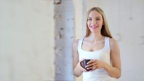 Portret uśmiechnięta Europejska kobiety mienia kubka pozycja przy studia lub domu loft białym tłem zbiory wideo