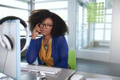 Portret uśmiechnięta kobieta z afro przy komputerem w jaskrawym szklanym biurze Obrazy Stock