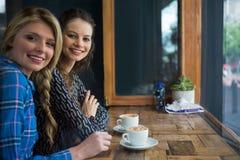Portret uśmiechnięta kobieta z filiżankami na stole w kawiarni Fotografia Royalty Free