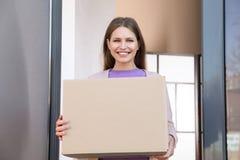 Portret uśmiechnięta kobieta z pakuneczkiem przy drzwi fotografia stock