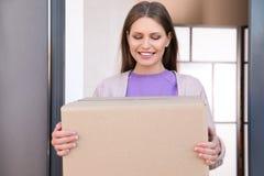 Portret uśmiechnięta kobieta z pakuneczkiem przy drzwi, mockup dla projekta zdjęcia stock