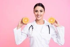 Portret uśmiechnięta kobiety lekarka z stetoskopu mienia pomarańczami odizolowywać fotografia royalty free