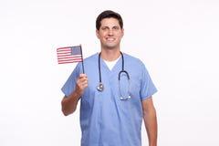 Portret uśmiechnięta męska pielęgniarki mienia flaga amerykańska Zdjęcia Royalty Free
