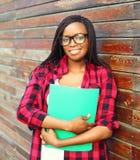 Portret uśmiechnięta młoda afrykańska kobieta trzyma skoroszytowego nadmiernego tło w szkłach Obraz Stock