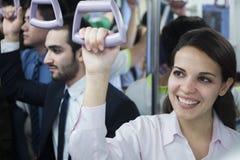 Portret uśmiechnięta młoda bizneswoman pozycja na metrze, patrzeje daleko od Zdjęcia Stock