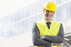 Portret uśmiechnięta młoda męska architekt pozycja zbroi krzyżującego outside budynek biurowego zdjęcia stock