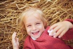 Portret uśmiechnięta mała dziewczynka kłama na ucho banatka Obrazy Royalty Free