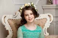 Portret uśmiechnięta mała dziewczynka siedzi o w kwiatu wianku Zdjęcie Stock