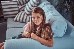 Portret uśmiechnięta mała dziewczynka z długim brown włosy i przebijanie spoglądamy, kłamający na kanapie w domu Obraz Stock