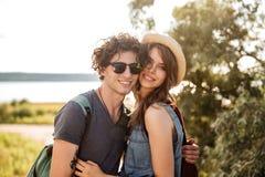 Portret uśmiechnięta modniś pary pozycja przeciw drzewom i morzu Obrazy Stock