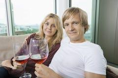 Portret uśmiechnięta para z win szkłami w żywym pokoju w domu Zdjęcia Royalty Free