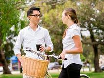 Portret uśmiechnięta pary pozycja w parku z roweru opowiadać Fotografia Stock