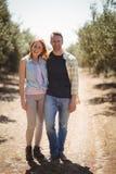 Portret uśmiechnięta potomstwo pary pozycja przy oliwki gospodarstwem rolnym na słonecznym dniu Zdjęcie Stock