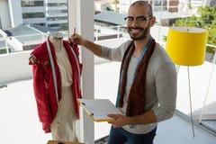Portret uśmiechnięta projektanta mienia schowka pozycja mannequin Zdjęcie Stock
