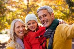 Portret uśmiechnięta rodzina przeciw drzewom Obrazy Stock