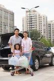 Portret uśmiechnięta rodzina z wózek na zakupy pozycją obok samochodu, outdoors zdjęcie stock