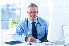 Portret uśmiechnięta samiec lekarka z dokumentem w szpitalu Obrazy Stock