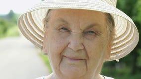 Portret uśmiechnięta stara kobieta ubierał w białym kapeluszu zbiory wideo