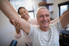 Portret uśmiechnięta starsza męska pacjenta i kobiety lekarka z rękami podnosić Obrazy Royalty Free