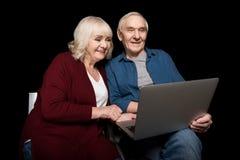 Portret uśmiechnięta starsza para używa laptop Zdjęcia Royalty Free