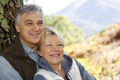 Portret uśmiechnięta szczęśliwa para opiera na drzewie Zdjęcie Royalty Free