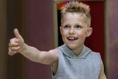Portret uśmiechnięta ufna chłopiec pokazuje kciuka szyldowego OK up Fotografia Royalty Free