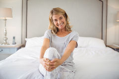 Portret uśmiechnięte kobiety siedzi z nogami krzyżował na łóżku Fotografia Royalty Free