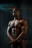 Portret uśmiechniętego amerykanina afrykańskiego pochodzenia męski bodybuilder z nagą półpostacią pozuje na czarnym pracownianym  Zdjęcia Stock