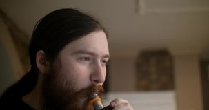 Portret uśmiechniętego mężczyzna relaksującego dymienia elektroniczny papieros zdjęcie wideo