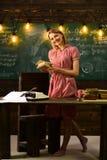 Portret uśmiechniętej młodej dziewczyny czytelnicza książka i stół Rozszerzamy twój umysł, czytamy a podczas gdy stojący przy szk Obraz Stock