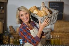 Portret uśmiechnięty żeński personel niesie łozinowego kosz różnorodni chleby przy kontuarem Obraz Royalty Free