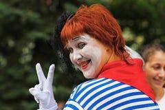 Portret uśmiechnięty żeński uliczny artysta pokazuje zwycięstwo znaka przy miasto dniem w Volgograd Zdjęcia Royalty Free